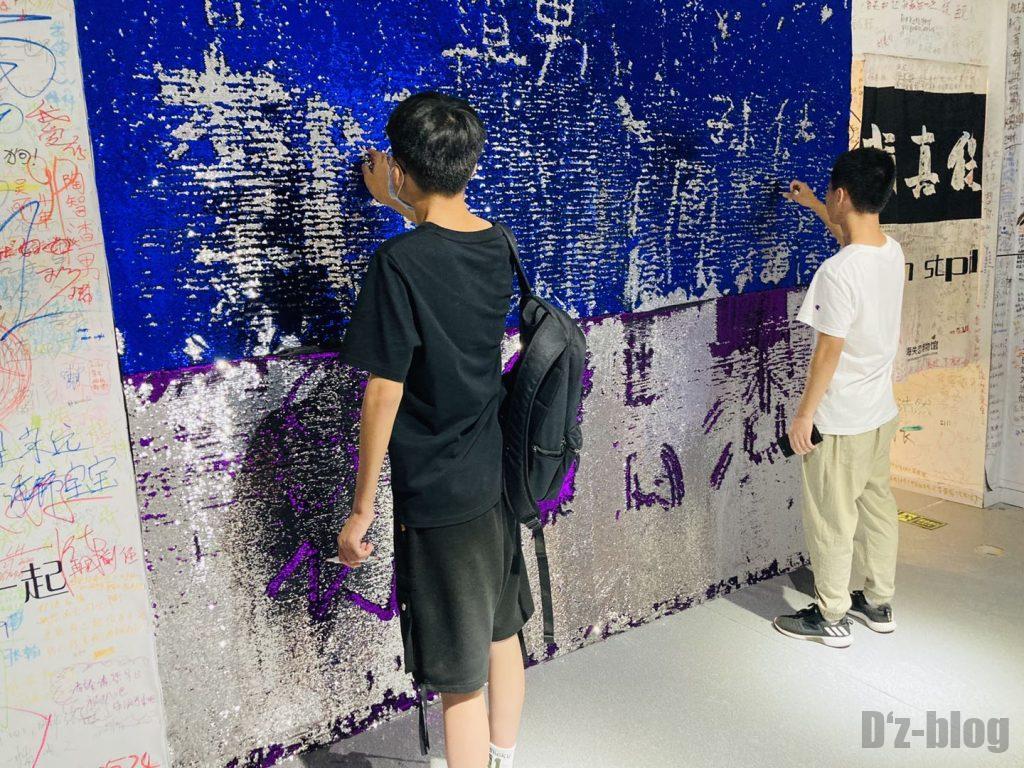 上海失恋博物館無言で壁に何かを各青年2人